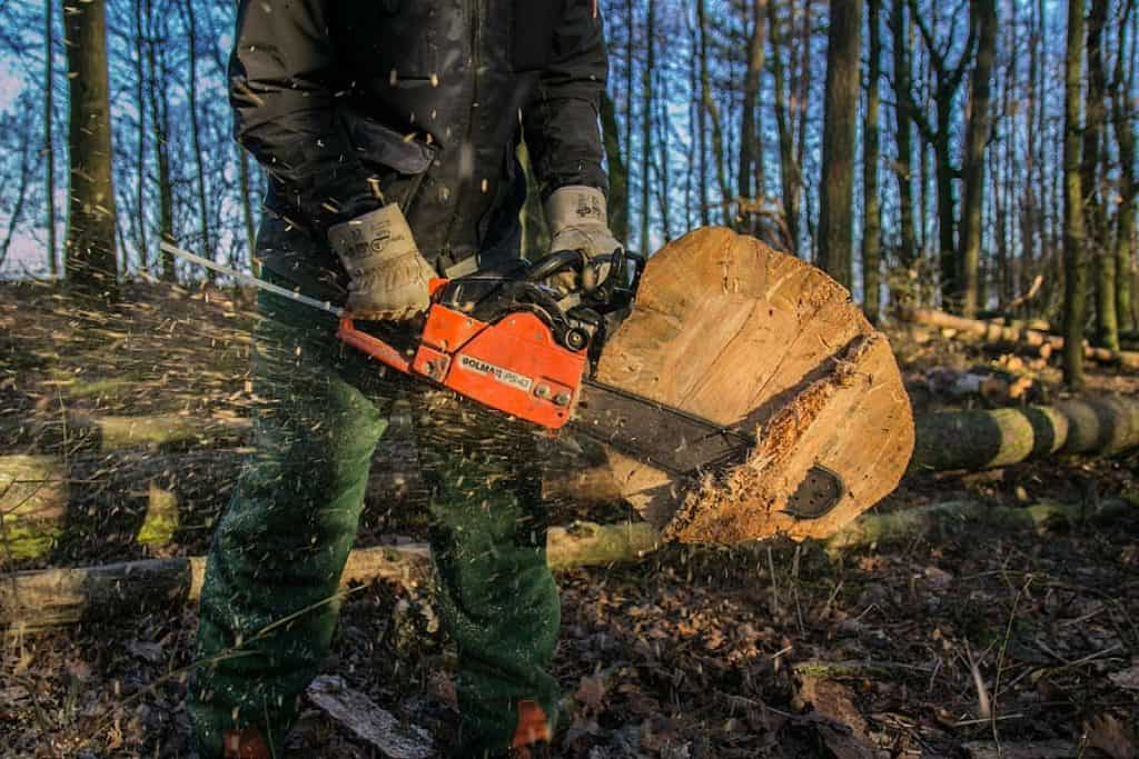 man is cutting the log with chainsaw