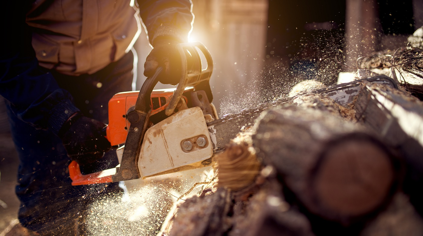 man is cutting the log with chainsaw at night