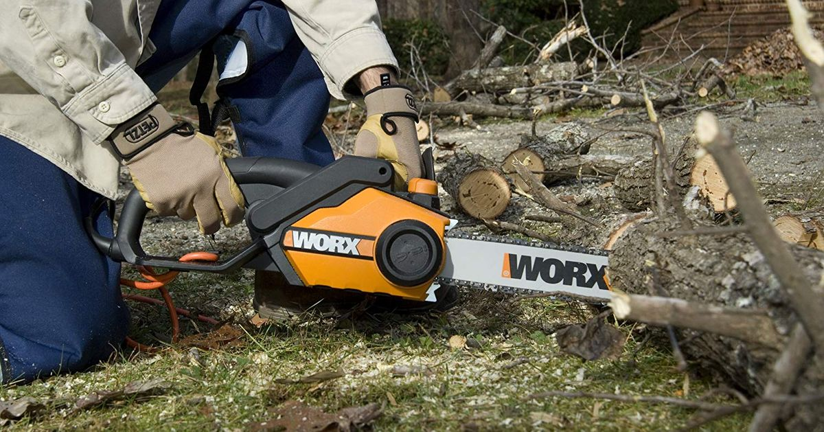 man is cutting the log with chainsaw WORX